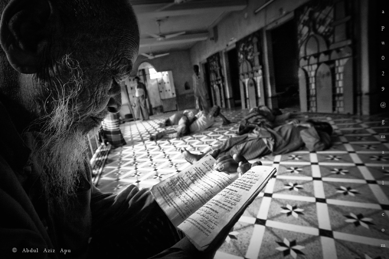 Old man reading quran while other sleep in a mosque